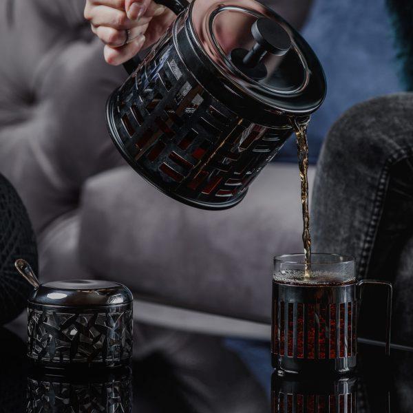Tetera negra sirviendo té en una taza